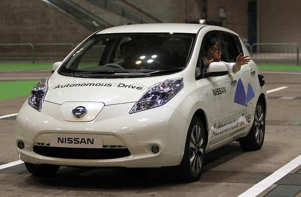 A staff member of Nissan gestures to the media as he rides its LEAF electronic car during a photo opportunity at CEATEC JAPAN 2013 in Chiba