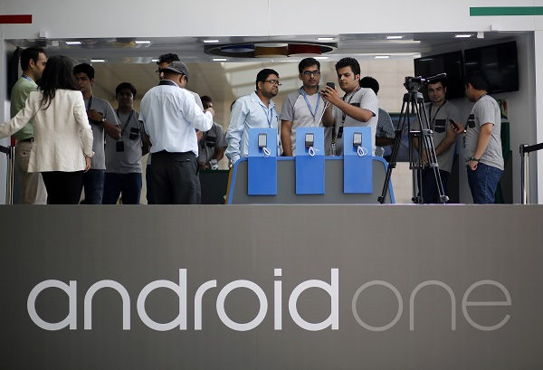 Visitors look at Android One based mobiles after its launch in New Delhi