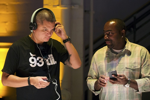 Men inspect Motorola's new Moto X phone by listening to music at a launch event in New York