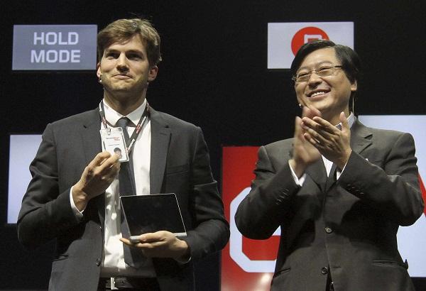 Aktor Ashton Kutcher (kiri) menunjukkan kartu identitas karyawan Lenovo bersama CEO Yang Yuanqing, dalam peluncuran tablet Android Yoga Lenovo di Beijing, 1 November 2013 silam. Saat ini Kutcher menjabat sebagai Product Engineer Lenovo.