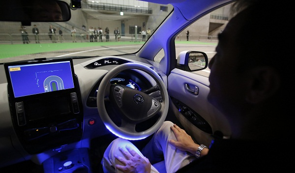 "A staff member of Nissan drives the LEAF electronic car with the aid of the new driving system ""Autonomous Drive"" during a photo opportunity at CEATEC JAPAN 2013 in Chiba"