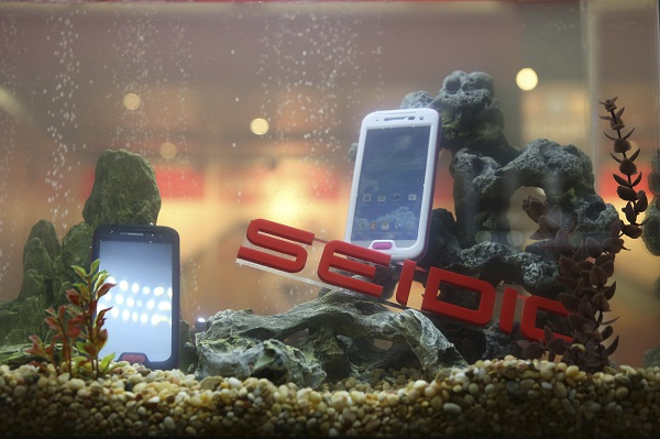 Seidic waterproof mobile phone cases by Obex are displayed in a fish tank at the annual Consumer Electronics Show in Las Vegas