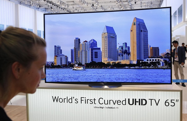 "A women looks at the world's first curved UHD TV 55"" 4K screen at the booth of Samsung during a media preview day at the IFA consumer electronics fair in Berlin"