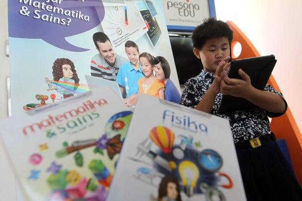 Seorang pelajar menggunakan tablet untuk mengakses buku pelajaran digital melalui aplikasi Pesona Edu.