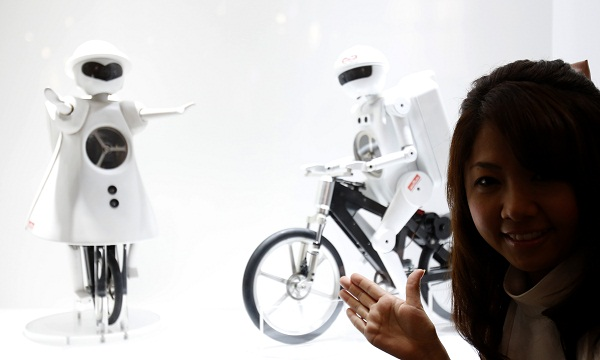 "A model poses with Murata Manufacturing Co Ltd's bicycle-riding robot ""Murata Seisaku-kun"" and unicycle-riding robot ""Murata Seikou-chan"" in Chiba"